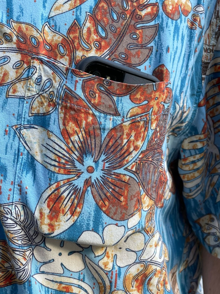 An iPhone peeking out of the left pocket of a blue & brown floral Hawaiian shirt.