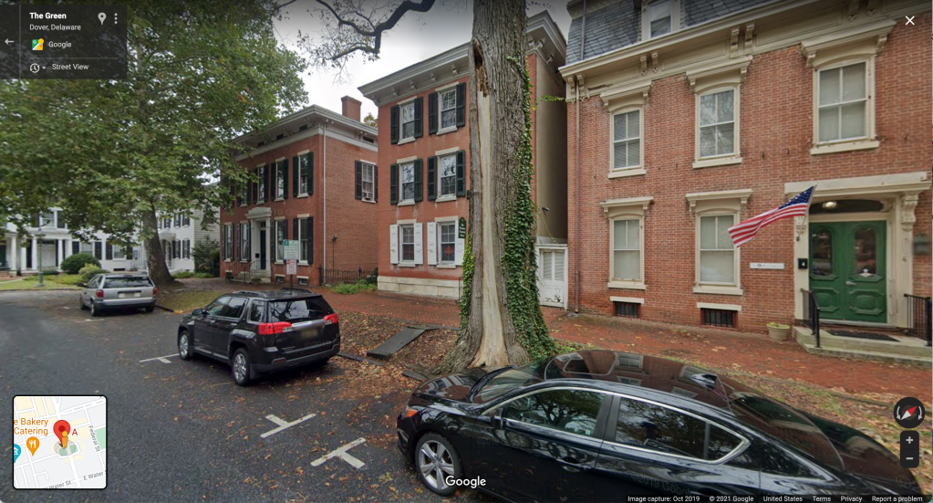 Screenshot of Google Streetview for the address 8 The Green Dover, DE 19901 shows a 3-story brick building with windows and shutters on what appears to be a residential street with limited parking and many trees.