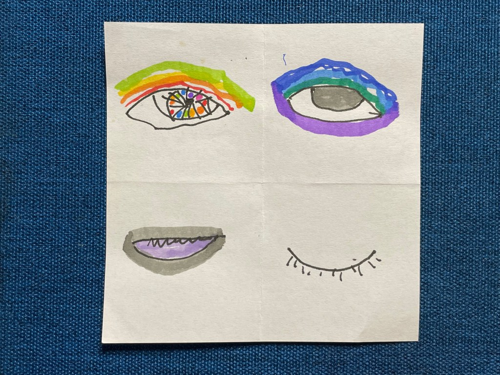 A square of white notepaper on a dark blue fabric background. The notepaper is folded into quarters, and in each quarter is roughly sketched an eye. Top left: a colorful eye with a rainbow iris; top right: a gray eye surrounded by purple, blue, and green; bottom left: a half closed eye showing lavender whites and surrounded by thick gray; bottom right: a closed eye.